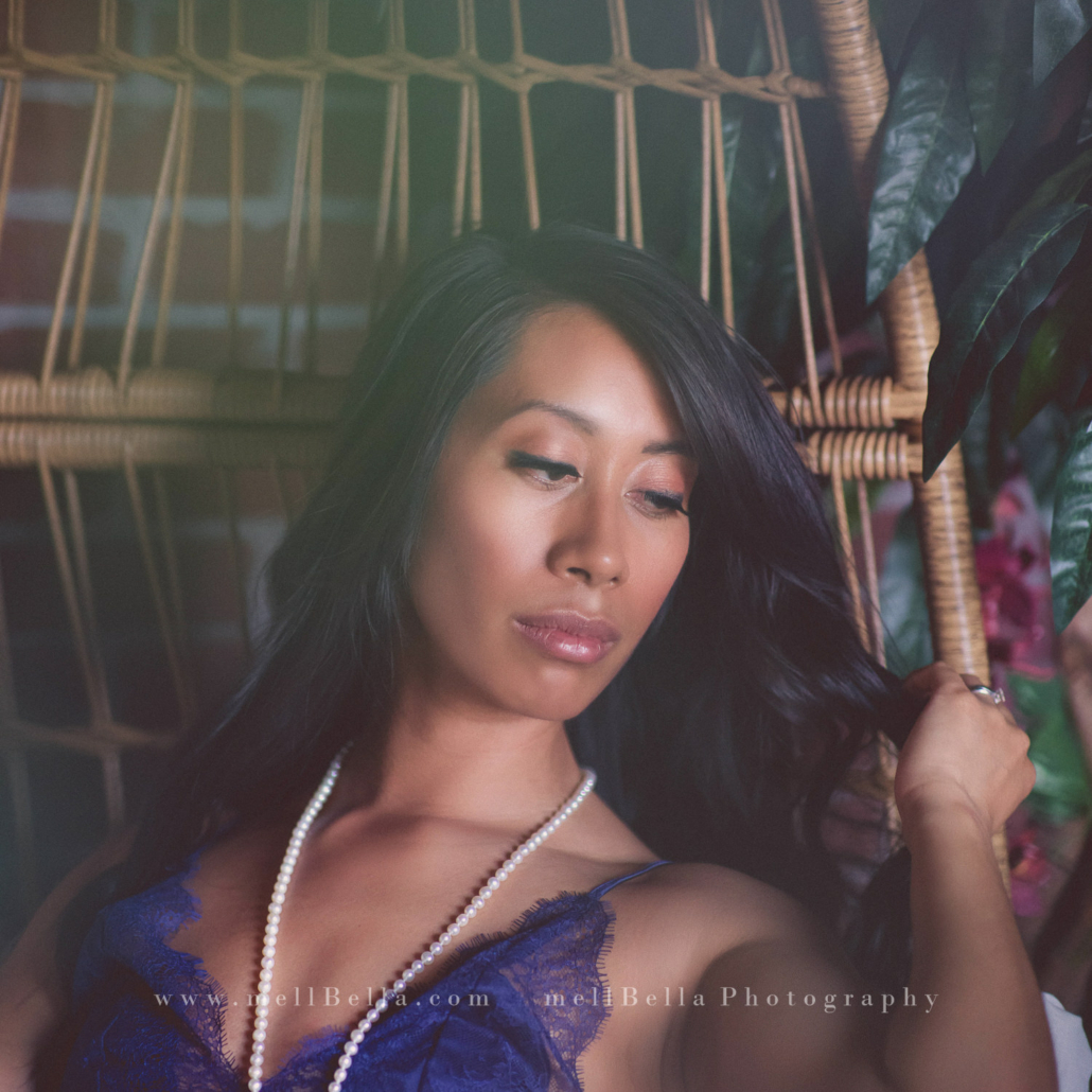 close up of woman with long black hair in a blue teddy and pearl necklace sitting in a rattan egg chair