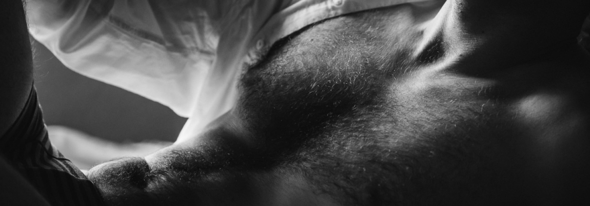 black and white close up of a male in a white unbuttoned shirt