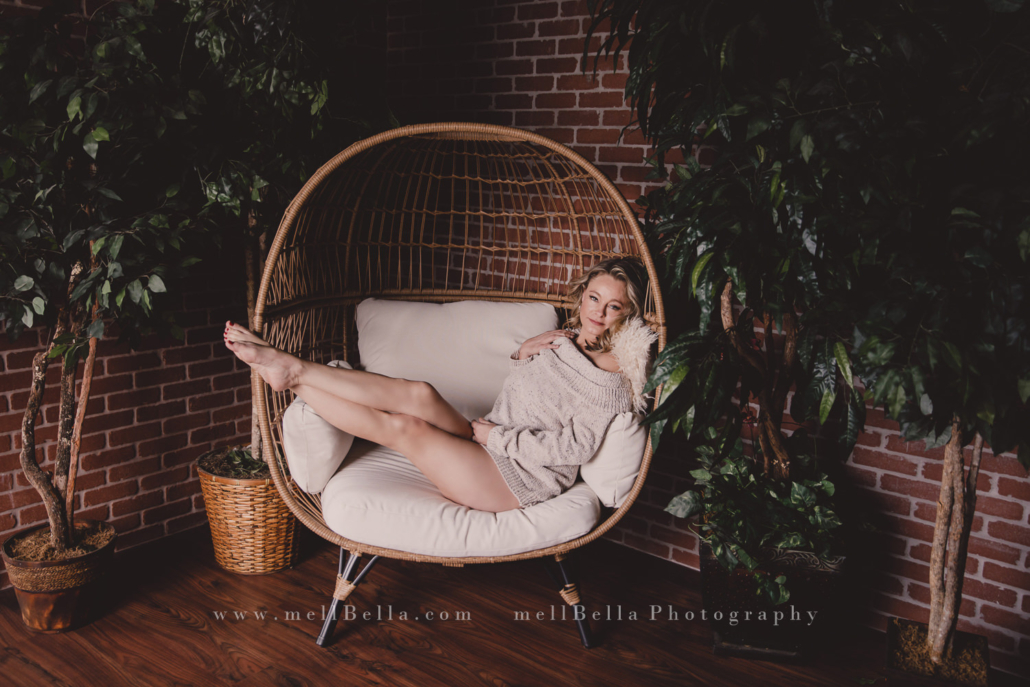 woman in cream sweater sitting on egg chair with feet propped up